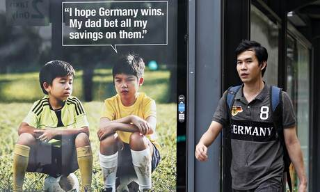 A man walks past a World Cup anti-gambling advertisement at a taxi stand in Singapore